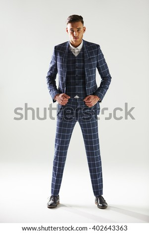 Full length portrait of young man wearing checked suit - stock photo