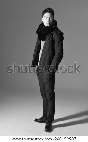 Full length portrait of young man with scarf standing with hands in pockets  - stock photo