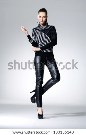 full-length portrait of young model posing on light background - stock photo