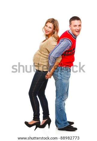 Full length portrait of young pregnant with husband having fun on white background - stock photo