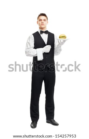Full length portrait of young serious waiter holding hamburger on plate isolated on white background - stock photo