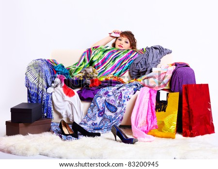 full-length portrait of young shopaholic woman with credit cards sitting tired behind sofa with a lot of clothes and shopping bags - stock photo