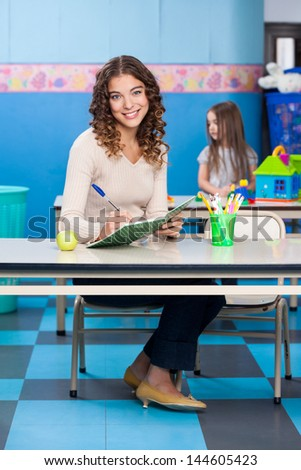 Full length portrait of young teacher writing in book with girl playing in background at kindergarten - stock photo
