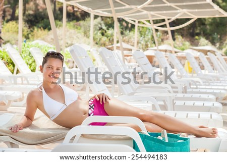 Full length portrait of young woman in swimwear relaxing on lounge chair at resort - stock photo