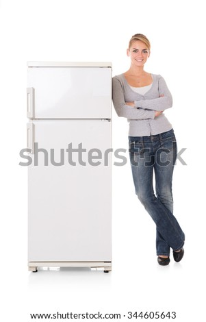 Full length portrait of young woman leaning on refrigerator over white background - stock photo