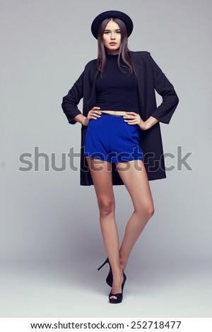 Full-length portrait young elegant woman in blue shorts, black jacket and hat. Fashion studio shot  - stock photo