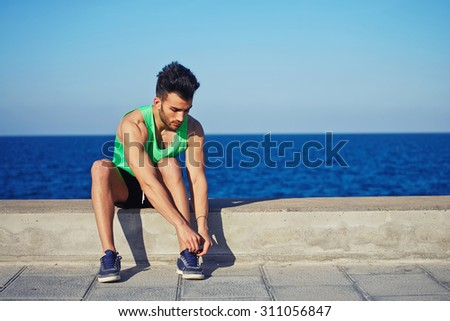 Full length portrait young fit man sat on concrete pier to tie the laces while rest after run along beach, male runner taking break after fitness training outdoors with copy space area for your text - stock photo
