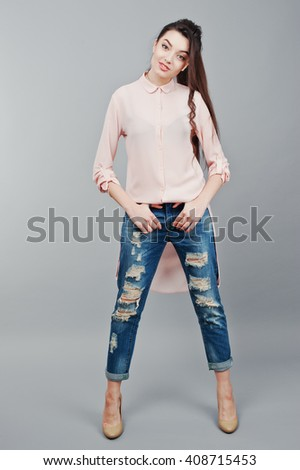 Full-length portrait young smiling brunette girl wearing in pink blouse, ripped jeans and cream shoes .Fashion studio shot - stock photo