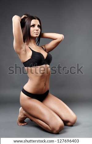 Full length profile of hot exotic dancer in sexy lingerie sitting on knees. Both hands in her hair. - stock photo