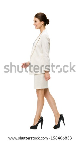 Full-length profile of walking businesswoman, isolated. Concept of leadership and success - stock photo