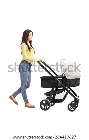 Full length profile shot of a young mother in casual clothes pushing a baby stroller isolated on white background - stock photo