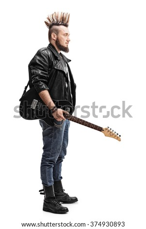 Full length profile shot of a young punk rocker holding an electric guitar isolated on white background - stock photo