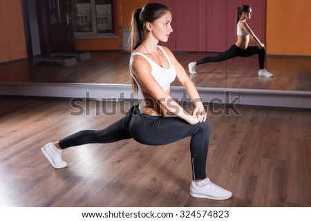 Full Length Profile View of Young Brunette Woman Wearing Exercise Clothing and Stretching in Leg Lunge Position with Straight Back in Dance Studio in front of Mirrors - stock photo