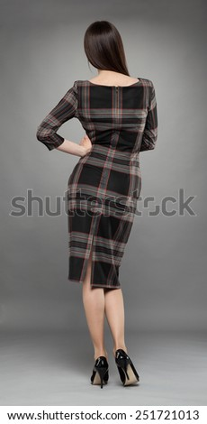 Full length rare view studio portrait of an attractive young brunette in dress on gray background - stock photo