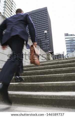Full length rear view of a businessman with briefcase ascending steps - stock photo