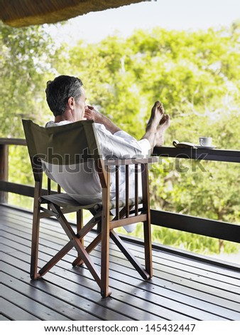 Full length rear view of a man in bathrobe sitting on chair in terrace with feet up - stock photo