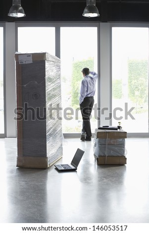 Full length rear view of a man looking out of glass door in empty office - stock photo