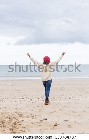 Full length rear view of a woman in casual warm wear stretching her arms on the beach - stock photo