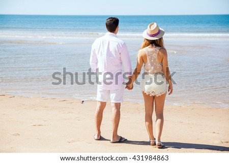 Full length rear view of a young couple holding hands and looking at the ocean during their vacation at the beach - stock photo