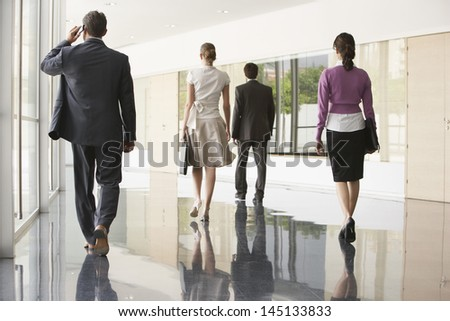 Full length rear view of business people walking on marble flooring in office - stock photo
