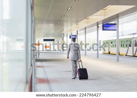 Full length rear view of businessman with luggage walking in railroad platform - stock photo