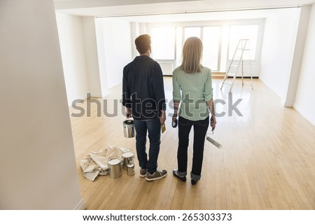 Full length rear view of mature couple with paint equipment standing on hardwood floor at home - stock photo