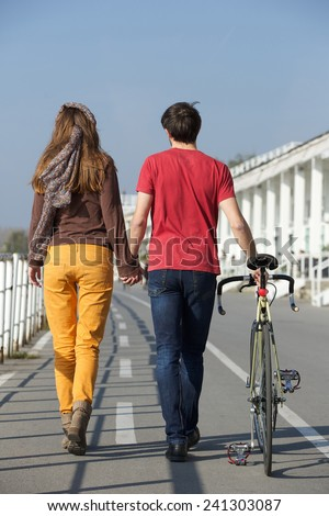 Full length rear view portrait of a young couple walking outdoors - stock photo