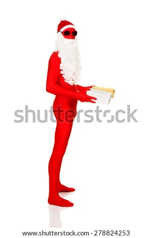 Full length santa in latex clothing holding gifts. - stock photo