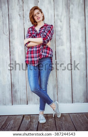 full length shot of a beautiful hipster woman, against a wooden background - stock photo