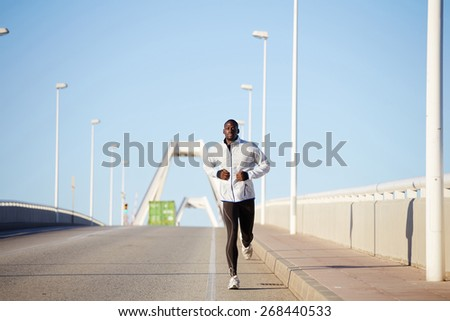 Full length shot of a fit man dressed in white windbreaker running on a bridge road at sunny day  - stock photo