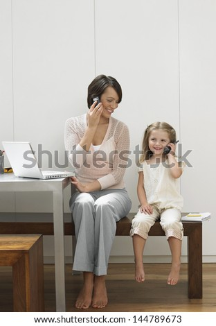 Full length shot of a happy mother and daughter using cellphones - stock photo