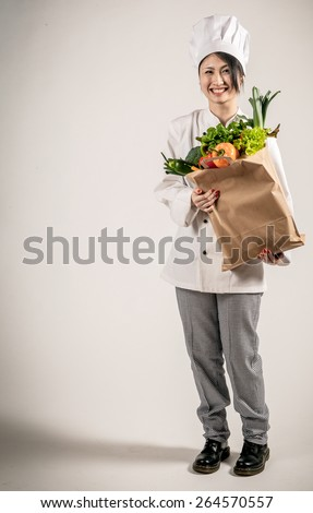 Full Length Shot of a Happy Young Female Chef Holding a Paper Bag Full of Fresh Vegetables While Looking at the Camera. Captured in Studio on a Gray Background. - stock photo