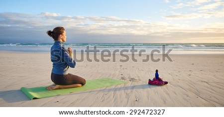 Full length shot of a kneeling young woman meditating on the beach early in the morning  - stock photo