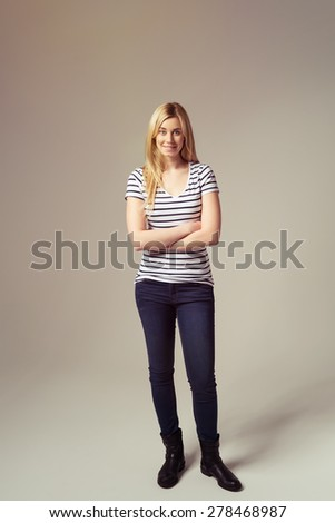 Full Length Shot of a Pretty Young Blond Woman in Trendy Outfit Standing Against Brown Background with Arms Closed. - stock photo