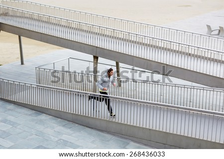 Full length shot of athletic male jogger running fast over little bridge at early morning - stock photo