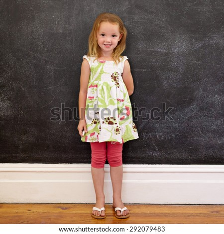 Full length shot of beautiful little girl standing against blackboard at home. She is holding a chalk looking at camera. - stock photo
