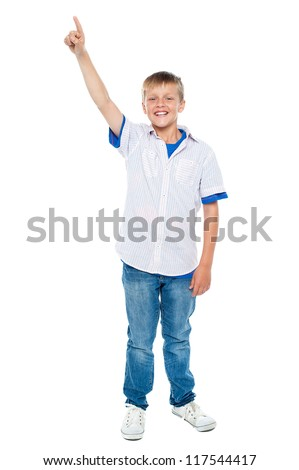 Full length shot of charming casual boy pointing upwards. Copyspace area - stock photo