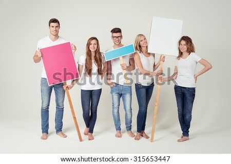 Full Length shot of Five Young Friends in Casual White Shirts and Jeans, Holding Empty Colored Placards and Smiling at the Camera Against White Background Inside the Studio - stock photo