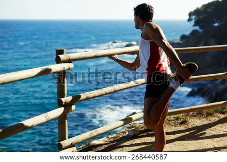 Full length shot of mature man stretching his hamstrings before a run outdoors at sunny day, athletic man enjoy the view while doing stretch exercise before a jog - stock photo
