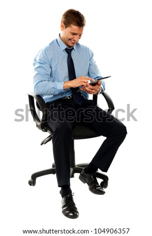 Full length shot of seated entrepreneur using electronic tablet - stock photo