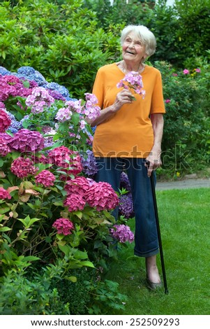 Full Length Shot of Thoughtful Old Woman Standing at the Garden with Flowers on Hand While Looking Up. - stock photo