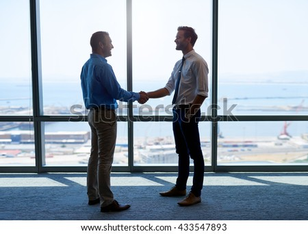 Full length shot of two businessmen shaking hands to acknowledge their partnership, and smiling positively, with a large office window behind them - stock photo