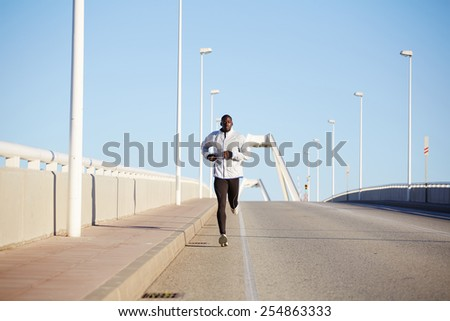 Full length shot of young sportive dark skinned runner training on the road against blue sky background  - stock photo