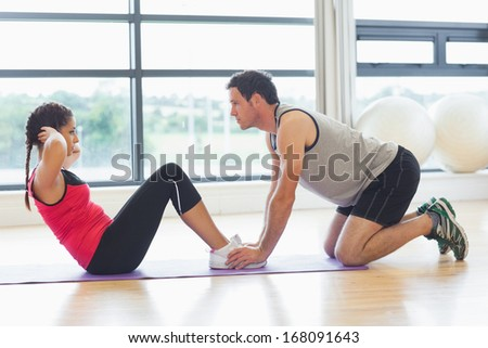 Full length side view of a male trainer helping young woman do abdominal crunches in the bright gym - stock photo