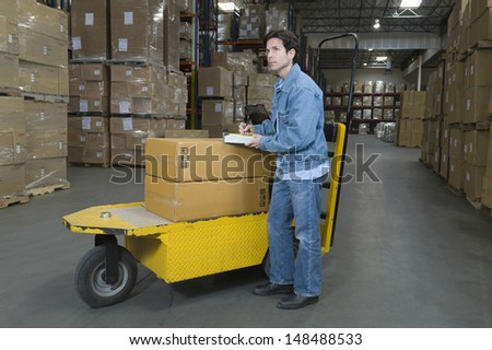 Full length side view of a man operating trolley in distribution warehouse - stock photo
