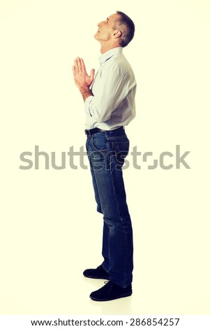 Full length side view of a man praying to God. - stock photo