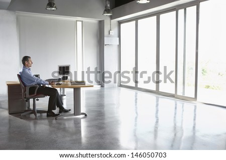 Full length side view of a man sitting at desk in empty office - stock photo