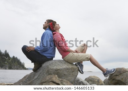 Full length side view of a young couple sitting back to back on rocks against ocean - stock photo