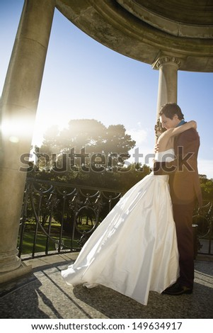 Full length side view of a young newlywed couple embracing - stock photo