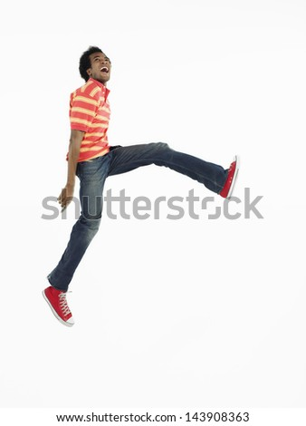 Full length side view of an Afro man jumping against white background - stock photo